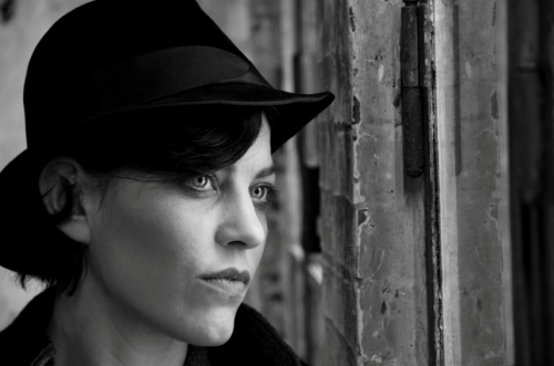 Black and white photo of woman with hat staring intently as if in deep thought