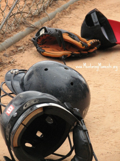 Baseball hat, batting helmets, and mitt laying beside fence. www.MentoringMoments.org