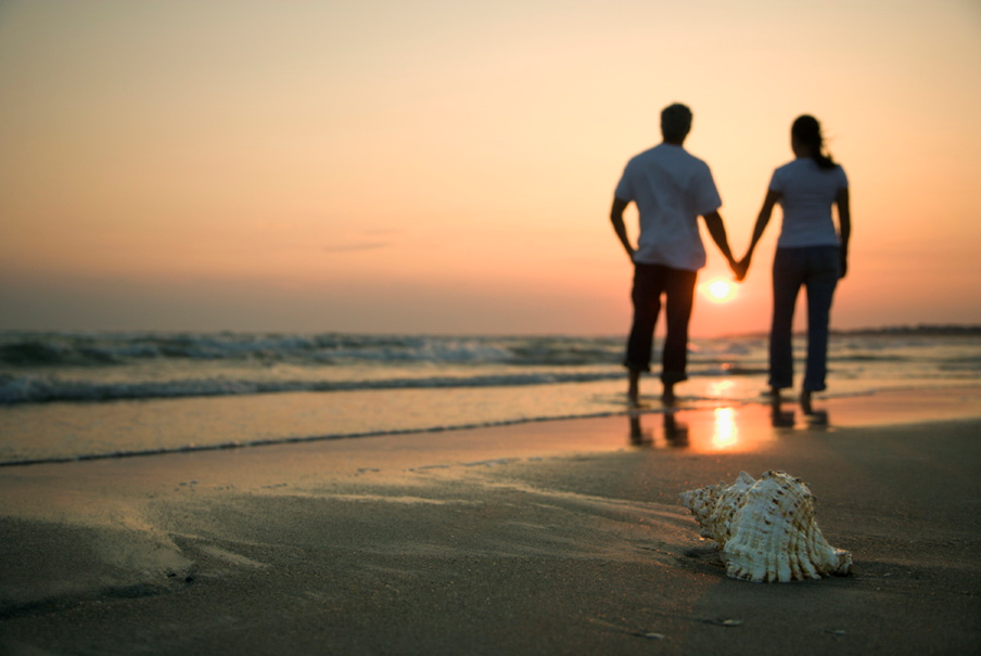 Couple watching sunset on the beach.
